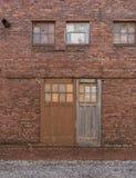 Vieilles portes de grange coulissantes sur le mur de briques extérieur de la vieille usine image libre de droits