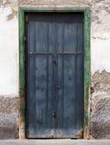 Vieilles portes doouble noires sur un mur de maison avec le plâtre de émiettage Photos stock