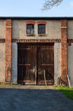 Vieilles portes fermées de grange de rustig dans le mur de briques rouge Porte rurale dans la lumière de coucher du soleil Photo stock