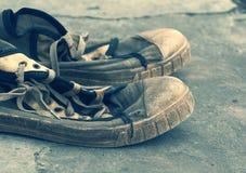 Vieilles rétros chaussures de gymnase sales sur le grunge un fond Vieilles chaussures de sports Photographie stock libre de droits