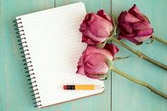 Vieilles roses et carnet vide Photographie stock libre de droits