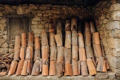 Vieilles tuiles de toit placées sur un mur en pierre d'une maison rurale images stock