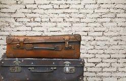 Vieilles valises de voyage de cru au-dessus de mur de briques images libres de droits