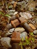 Vieilles vis rouillées s'étendant sur le chemin en pierre photos stock