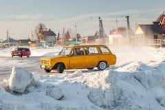 Vieilles voitures russes Lada préparé pour emballer la commande sur la glace sur un lac congelé, dériver et se déplacer un treuil photos libres de droits
