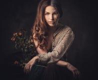 Vieillissant, concept de soins de la peau Demi vieille demi jeune femme avec le bouquet rose fané photographie stock