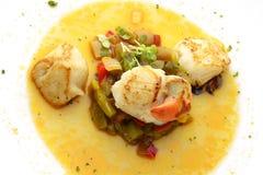 Vieiras assadas do prato de peixes com cebolas e pimentas na sopa Fotografia de Stock