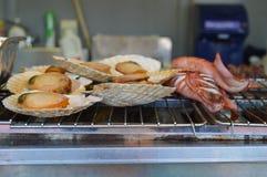 Vieiras e calamares grelhados em um torrador no festival da cerveja, Japão Fotografia de Stock Royalty Free
