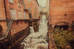 Vieja área industrial con las fábricas y la corriente del wWater de una pequeña cascada en Goteburgo, Suecia fotografía de archivo