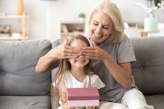 Vieja abuela de amor que hace presente a poca muchacha feliz del niño imagen de archivo