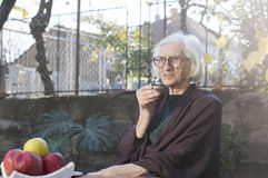 Vieja abuela que come la taza de café al aire libre Imágenes de archivo libres de regalías
