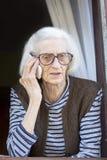 Vieja abuela que habla en el teléfono que se coloca en su ventana Imágenes de archivo libres de regalías