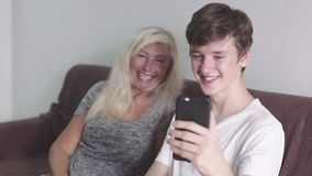 Vieja abuela y nieto adulto que usa la aplicación móvil en el tougether del teléfono que asienta en el sofá Hacer la llamada vide metrajes