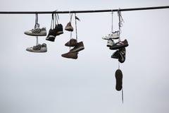 Vieja caída de las botas en el cable eléctrico Fotografía de archivo