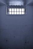 Vieja celda de prisión con la ventana barrada Foto de archivo libre de regalías