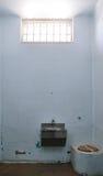 Vieja celda de prisión con la ventana barrada Imagen de archivo libre de regalías