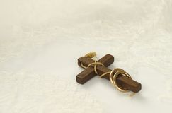 Vieja cruz de madera con los anillos de oro en el cordón blanco Imagen de archivo