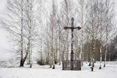 Vieja cruz de madera en un pequeño parque de abedules en invierno Imagen de archivo