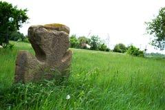 Vieja cruz de piedra en un prado verde Imagen de archivo libre de regalías