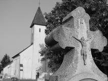 Vieja cruz en cementerio con un templo Imagen de archivo