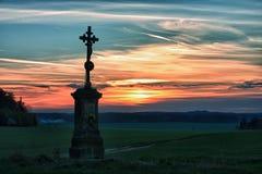 Vieja cruz en puesta del sol Imágenes de archivo libres de regalías