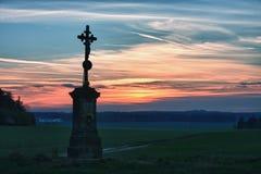 Vieja cruz en puesta del sol Foto de archivo libre de regalías