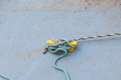 Vieja cuerda azul atada para amarillear el listón en el embarcadero concreto Imagen de archivo