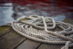Vieja cuerda de la nave en un embarcadero de madera foto de archivo libre de regalías