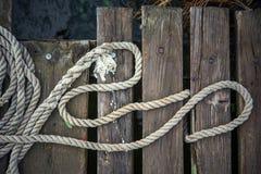 Vieja cuerda de la nave en un embarcadero de madera Imagen de archivo
