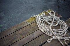 Vieja cuerda de la nave en un embarcadero de madera Fotografía de archivo libre de regalías