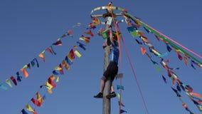 Vieja diversión rusa de la tradición: el hombre sube al top del polo de madera para los premios y los regalos