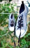 Vieja ejecución azul de la zapatilla de deporte en una cuerda detrás de una pinza de madera Fotografía de archivo