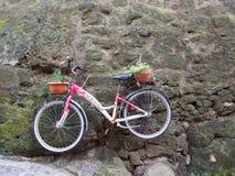 Vieja ejecución roja de la bicicleta en una pared de piedra Foto de archivo