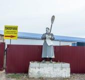 Vieja escultura de un hombre en un abrigo largo Imagen de archivo