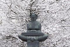 Vieja escultura en el fondo de la nieve del invierno Imagenes de archivo