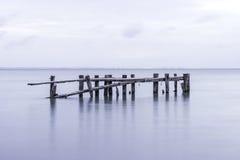 Vieja estructura del embarcadero que cae abajo, posts que se colocan en el lago tranquilo Fotos de archivo