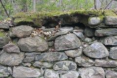 Vieja fundación de la pared de la roca con el musgo y las hojas Foto de archivo