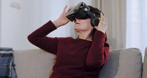 Vieja generación una mujer en la edad usando los vidrios de una realidad virtual muy la impresionan por primera vez sobre esto metrajes
