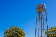 Vieja hilera de árboles de Rusty Water Tank Tower Above Imagenes de archivo