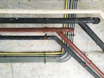 Vieja línea de los tubos en la pared del cemento Foto de archivo