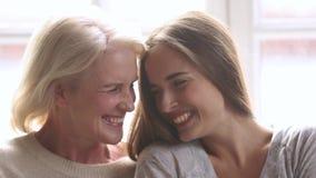 Vieja madre feliz e hija joven que ríen mirando la cámara almacen de metraje de vídeo