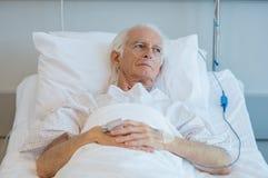 Vieja mentira paciente en cama Imagenes de archivo