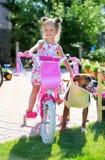 Vieja muchacha de cuatro años linda en una bicicleta con un perro Fotos de archivo libres de regalías