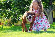 Vieja muchacha de cuatro años linda que juega con su perro Fotografía de archivo