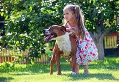 Vieja muchacha de cuatro años linda que juega con un perro Imágenes de archivo libres de regalías