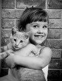 Vieja muchacha de dos años con un gatito fotografía de archivo