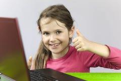 Vieja muchacha de siete años con la computadora portátil Fotografía de archivo