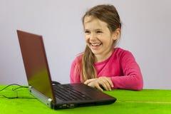 Vieja muchacha de siete años con la computadora portátil Imagen de archivo