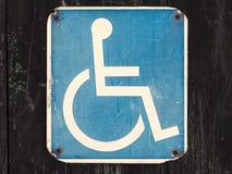 Vieja muestra del sillón de ruedas en una pared de madera Imágenes de archivo libres de regalías
