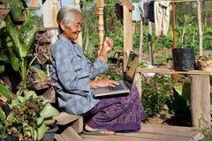 Vieja mujer asiática con la computadora portátil Foto de archivo libre de regalías